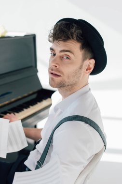 selective focus of handsome musician sitting by piano and looking at camera