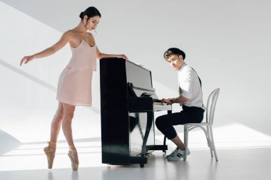 handsome pianist playing while beautiful ballerina dancing near piano