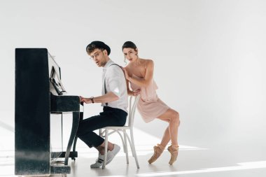 attractive ballerina touching handsome musician playing piano
