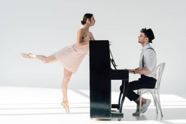 handsome musician playing while graceful ballerina dancing near piano