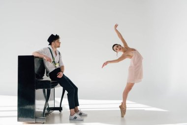 handsome musician holding rose and looking at dancing beautiful ballerina