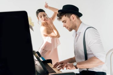 selective focus of handsome musician playing piano while attractive ballerina dancing near him