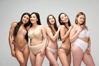 five smiling pretty multicultural girls isolated on grey, body positivity concept