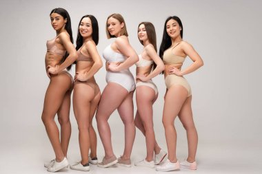 five young multiethnic women in lingerie posing with hands on hips, body positivity concept