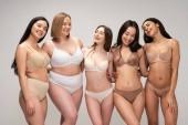 pět usmívající se multikulturní dívky ve spodním prádle objímají při Pózování na kameru, samostatný na šedé, tělo pozitivity konceptu