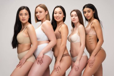 Five attractive multicultural girls in underwear posing at camera and smiling isolated on grey, body positivity concept stock vector