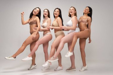five cheerful multiethnic girls in underwear dancing at camera, body positivity concept