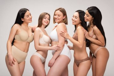 five multiethnic cheerful young women smiling and posing at camera isolated on grey, body positivity concept