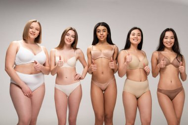 five pretty multicultural girls in lingerie showing thumbs up isolated on grey, body positivity concept
