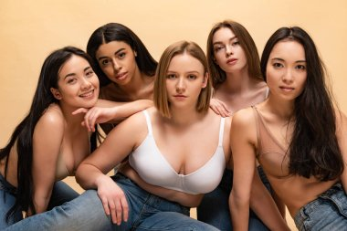 five pretty multicultural girls sitting and looking at camera isolated on beige, body positivity concept
