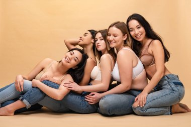 five smiling multicultural women sitting together and leaning on each other, body positivity concept