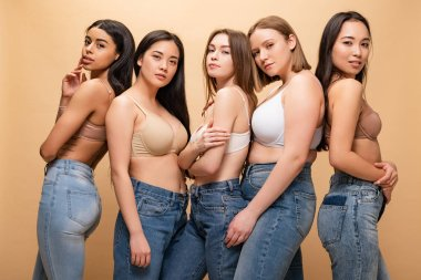 five beautiful multicultural girls posing at camera isolated on beige, body positivity concept