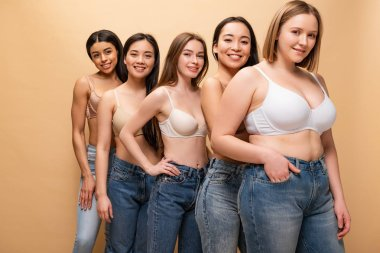 Five pretty multicultural girls in blue jeans and bras smiling and looking at camera isolated on beige, body positivity concept stock vector