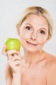beautiful mature woman holding green apple and looking at camera on grey background