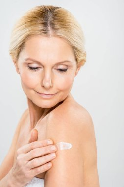 beautiful and mature woman looking down and applying cosmetic cream on shoulder isolated on grey