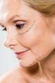 Fotografia Chiuda in su della donna invecchiata bella e centrale con le linee sul volto guardando giù isolato su bianco