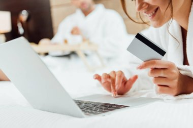 Cropped view of cheerful woman using laptop while holding credit card near boyfriend stock vector