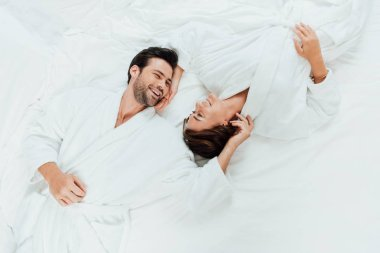 top view of happy couple in bathrobes looking at each other while lying on bed