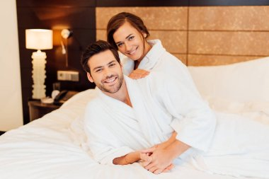 Handsome man and happy girlfriend in white bathrobes hugging and looking at camera while lying on bed stock vector