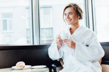 Attractive brunette woman in bathrobe smiling and holding cup of coffee stock vector