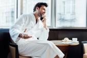 glücklicher bärtiger Mann im weißen Bademantel, der am Kaffeetisch mit Frühstück auf dem Smartphone spricht