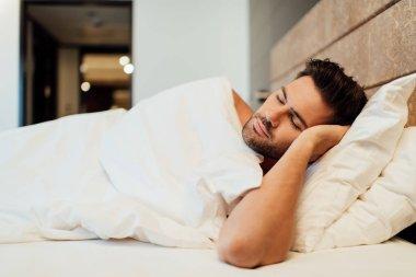 Selective focus of handsome bearded man sleeping in bed stock vector