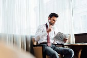 selective focus of handsome man in suit sitting near coffee table while reading newspaper and holding cup of coffee