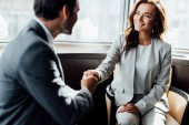 Photo selective focus of happy businesswoman shaking hands with businessman
