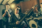 Fotografie selective focus of stylish guitarist in sunglasses playing electric guitar near rock band