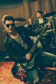 selective focus of guitarist in sunglasses playing electric guitar near drummer