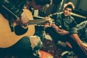 Fotografie selective focus of musician playing acoustic guitar near friends