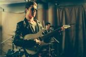 Selektivní fokus člověka hraje na kytaru elecric poblíž bubeník