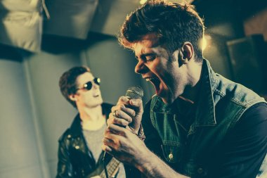 selective focus of stylish singer singing in microphone near rock band
