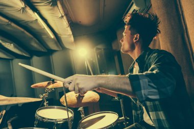 handsome musician holding drum sticks and playing drums