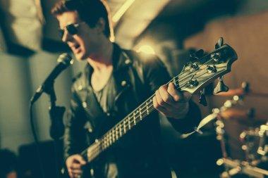 selective focus of electic guitar in hands of guitarist singing song in microphone