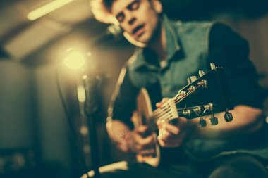 selective focus of acoustic guitar in hands of singer near microphone