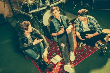 overhead view of happy rock band talking while sitting on carpet near musical instruments