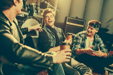 selective focus of happy rock band laughing while talking and holding paper cups