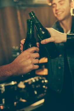 cropped view of men clinking bottles with beer