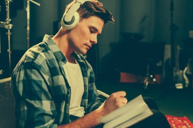 serious young composer listening music in headphones while writing in notebook