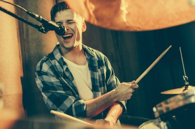 selective focus of handsome man singing in microphone while playing drums
