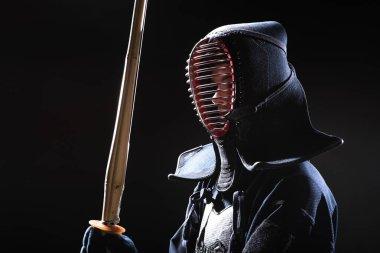 Kendo fighter in helmet holding bamboo sword on black stock vector
