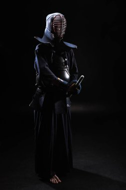 Full length view of kendo fighter in helmet holding bamboo sword on black stock vector