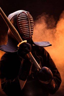 Kendo fighter in armor holding bamboo sword in smoke stock vector