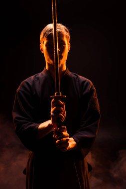 Young man in kimono holding kendo sword on black stock vector