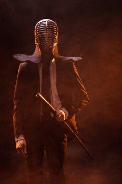Kendo fighter in formal wear and helmet holding bamboo sword on dark stock vector