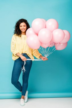 Attractive african american girl holding pink air balloons on blue stock vector