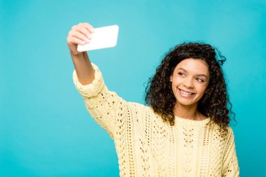 Happy curly african american woman taking selfie on smartphone isolated on blue stock vector