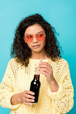 attractive african american girl in sunglasses holding bottle with straw isolated on blue