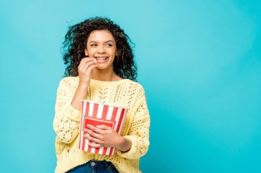 cheerful curly african american woman eating popcorn isolated on blue